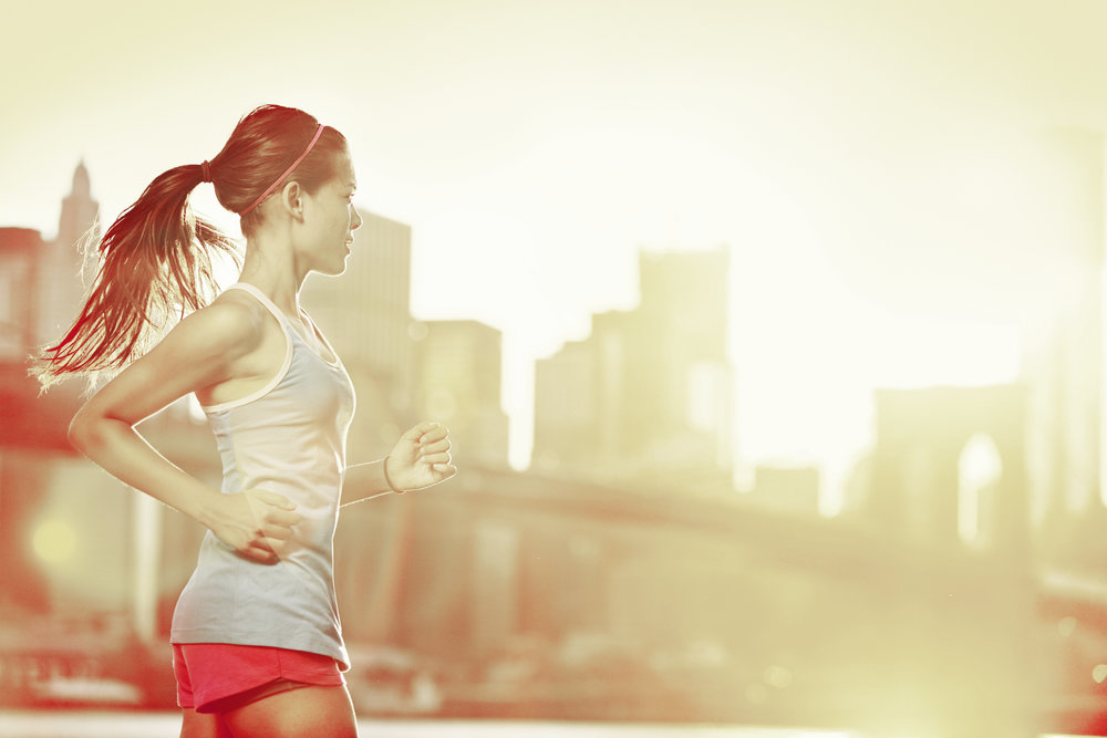 Woman running with a city skyline as the backdtop