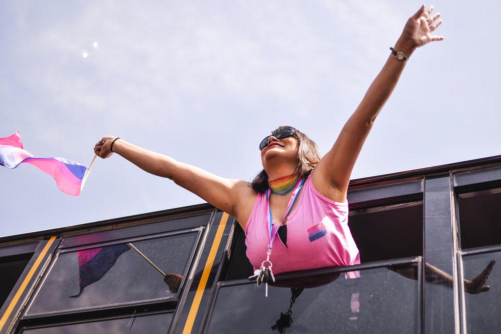 A Albuquerque Public Schools employee hangs from a school bus during the 2016 Pride Parade Saturday, June 11, 2016 in Albuquerque, New Mexico.