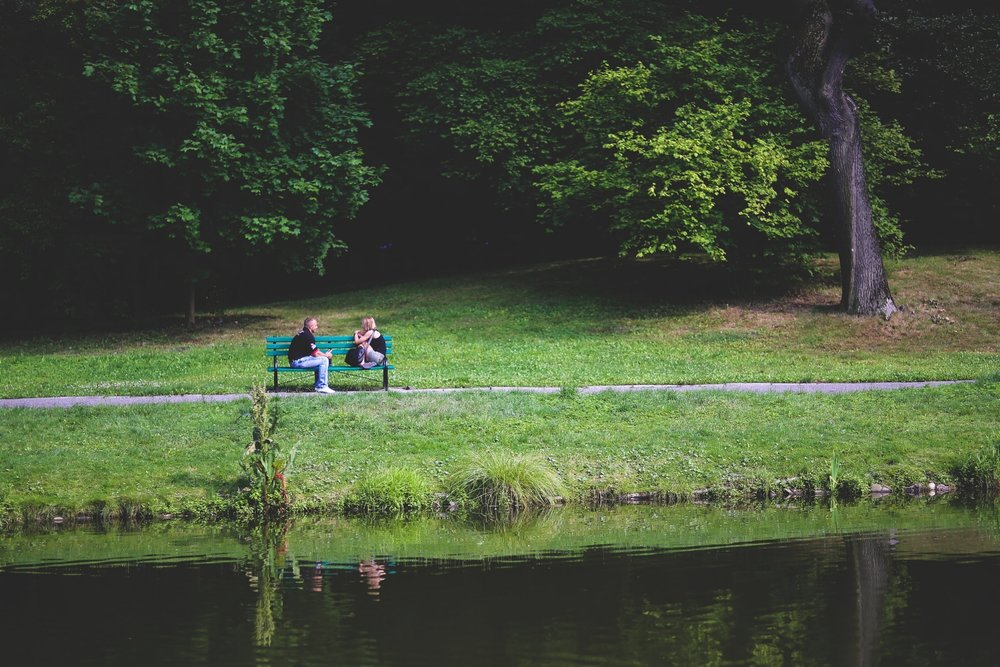 Two people talking on a bench outside
