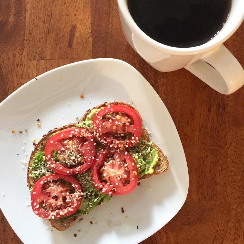 Breakfast  Av ocado  toast with tomato slices, hemp seeds, chili flakes and my must-have: coffee.