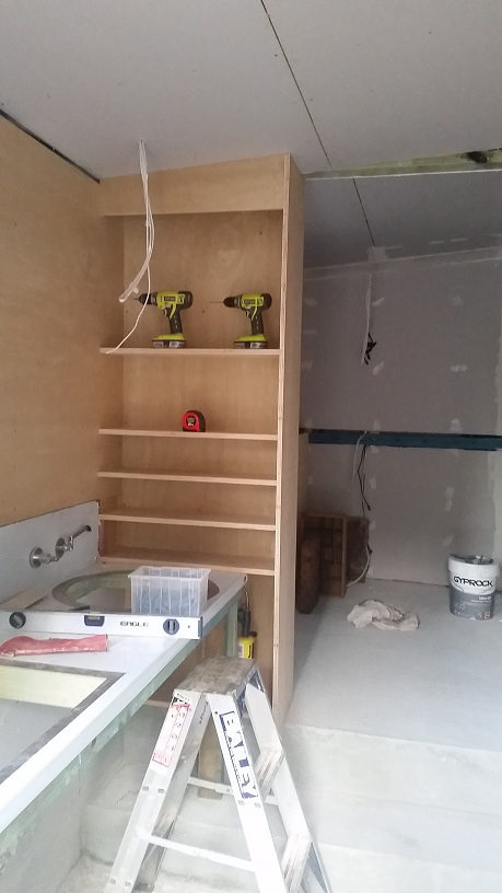 a new highly functional workzone adjacent to the carport with built in shelving, sinks, flush mounted recycled lockers (not visible in this view), built in sound system, gyprock with insulation ....