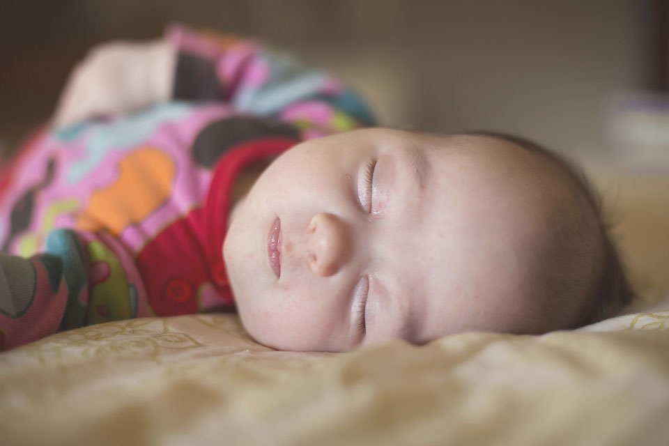 Newborn baby girl sleeping in bed