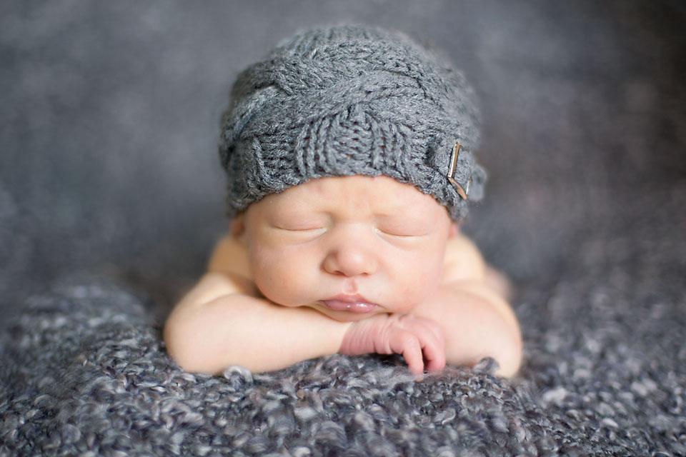 Newborn Baby Boy Head on Arms Sleeping on Grey Blanket with Grey Hat