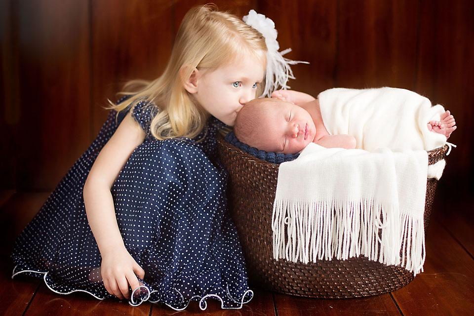 Big Sister Kissing Newborn Baby Boy on Head