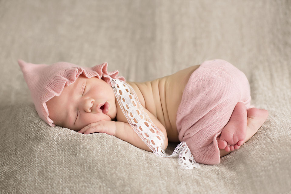 Newborn baby girl in pink bloomers and pink bonnet