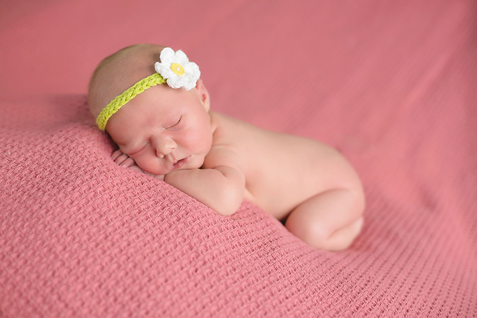Newborn baby girl with flower bow sleeping on pink blanket
