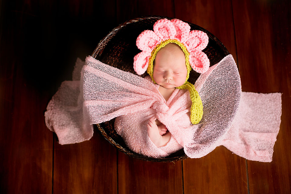 Newborn baby girl in flower bonnet and pink knotted wrap in basket on wood floor