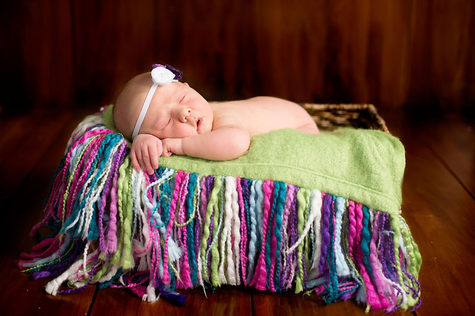 Newborn baby girl in basket with fringe on wood floor