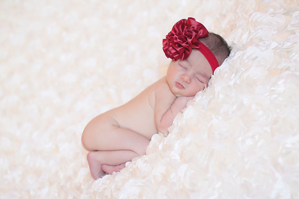 Newborn baby girl with red bow on white satin.