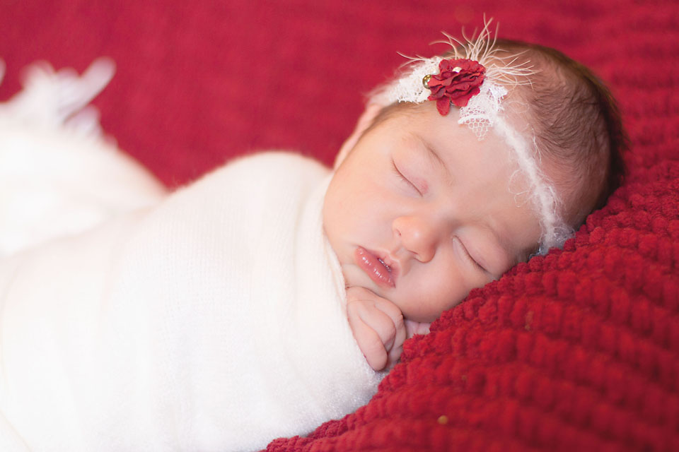 Newborn baby girl wrapped in white on red blanket with cute bow.
