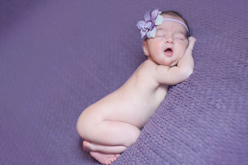 Newborn baby girl sleeping on purple blanket with purple bow.