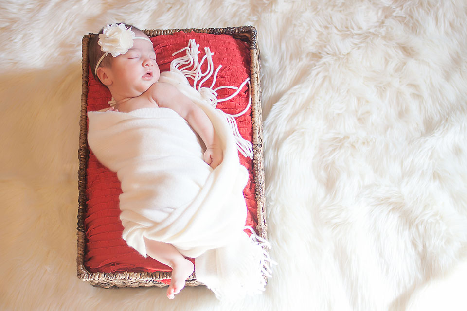 Newborn baby girl in basket with red ruffle fabric wrapped in white.
