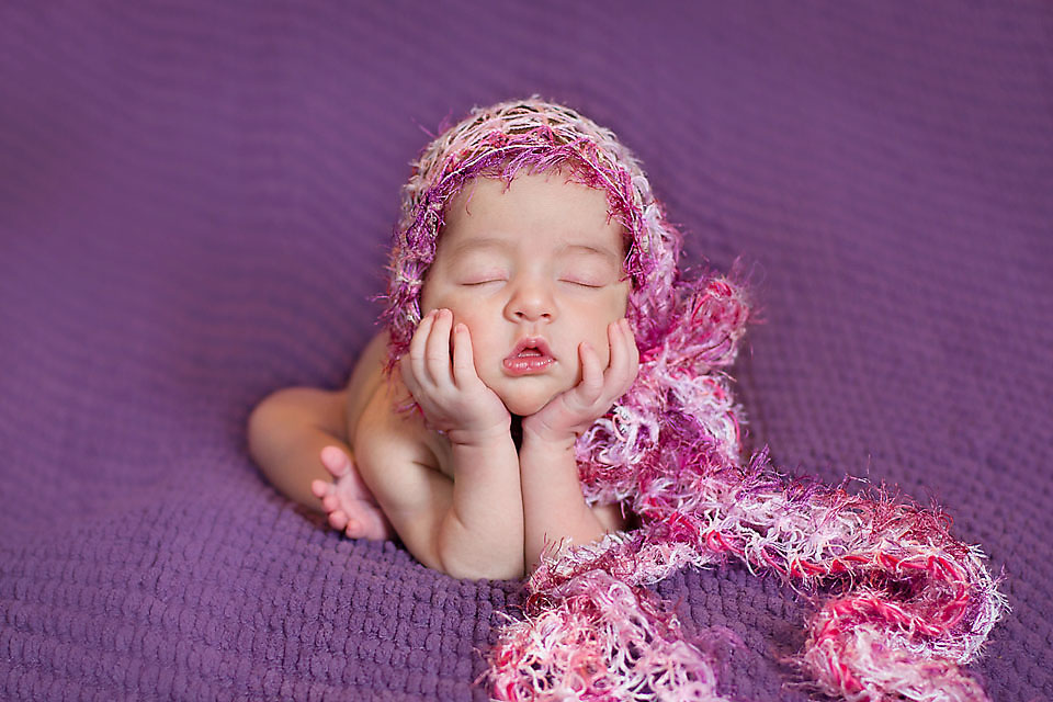 Newborn baby girl head in hands with pink bonnet on purple blanket.
