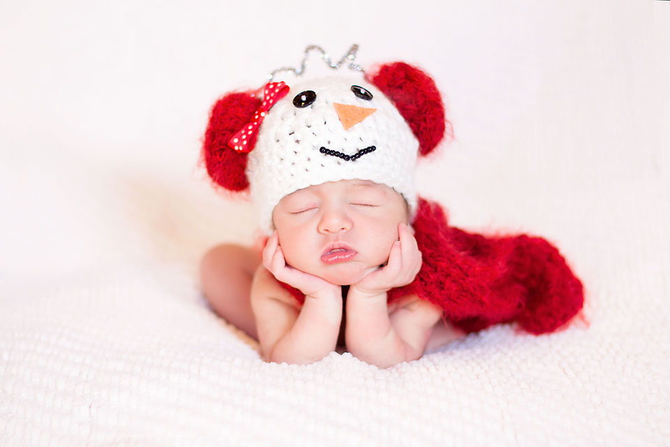 Newborn Baby girl in snowman hat and scarf on white blanket Christmas newborn