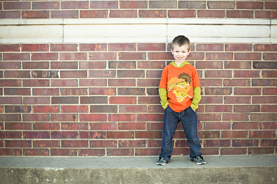 Cute little boy by brick wall portrait