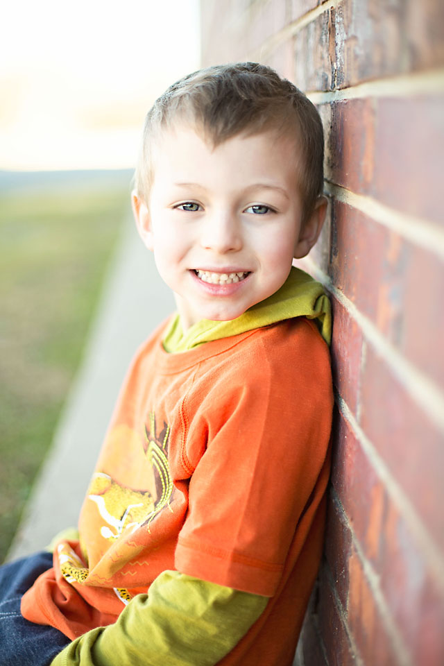 Little boy by brick wall portrait