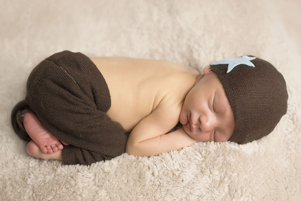 Cute little newborn baby boy in brown knit pants and star hat