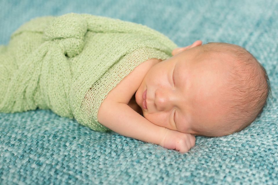 Cute little newborn baby boy wrapped in green on blue blanket