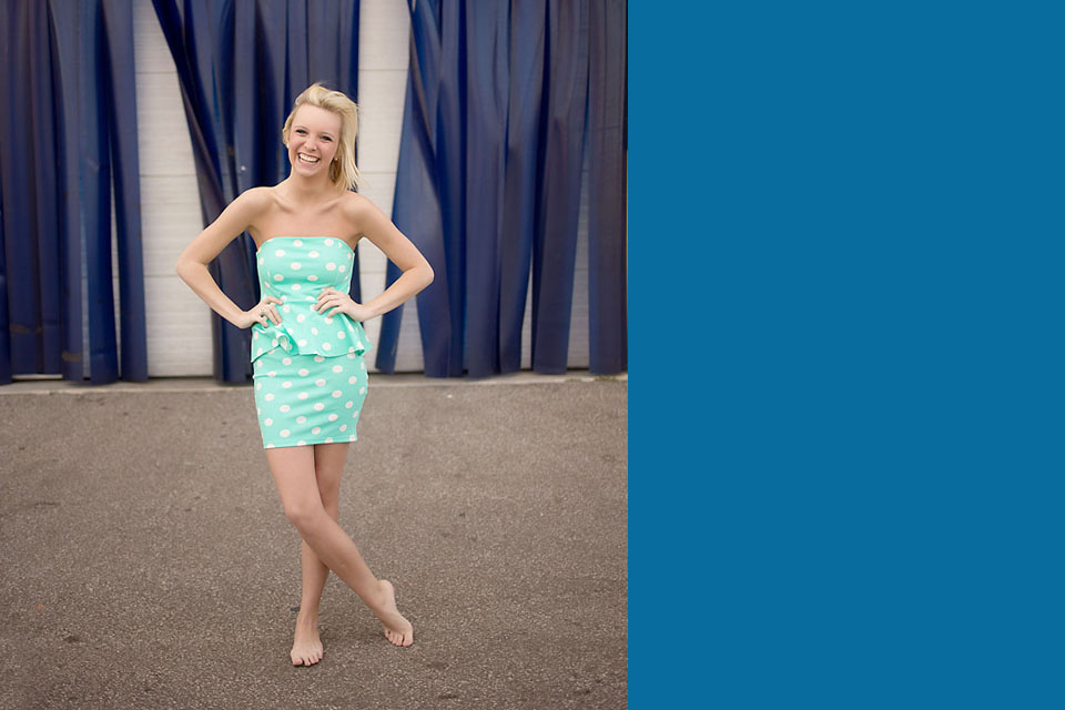 Beautiful senior girl in fron of blue wall with polka dot dress
