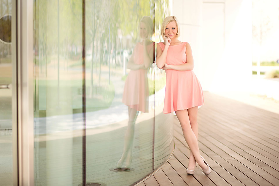Beautiful senior girl standing pose with reflection on glass