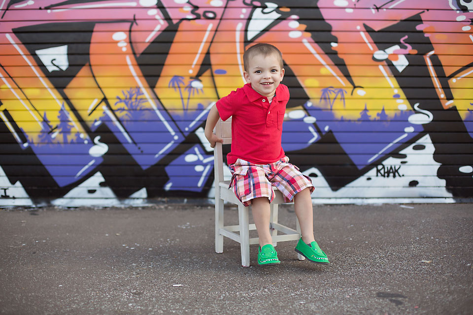 Little boy on chair in front of graffiti wall.