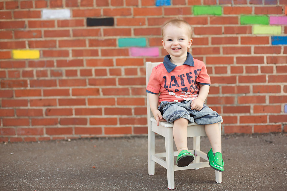 Cute little boy on chair in front of painted wall