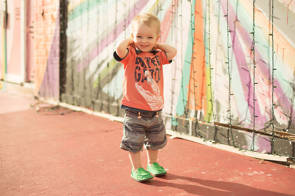 Cute little boy in front of rainbow painted wall hazy