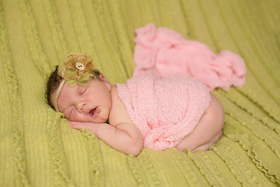 cute baby girl laying on green blanket with pink wrap and bow