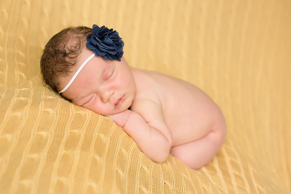 Cute Oklahoma newborn baby girl with blue bow on yellow blanket