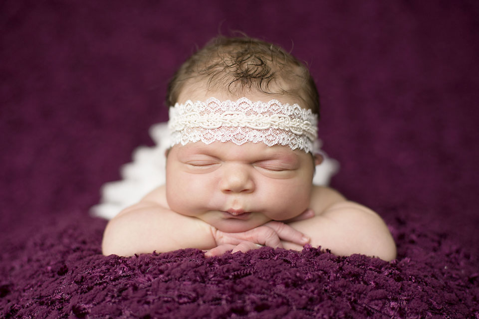 Cute oklahoma newborn baby girl head on hands with lace bow