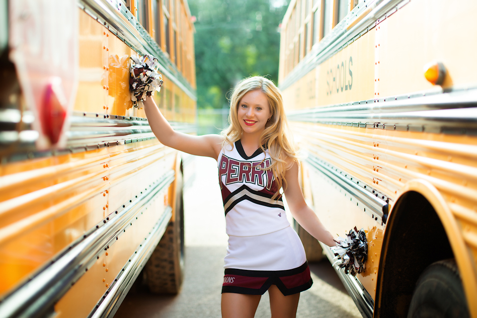 Senior girl in cheer uniform in between school buses.