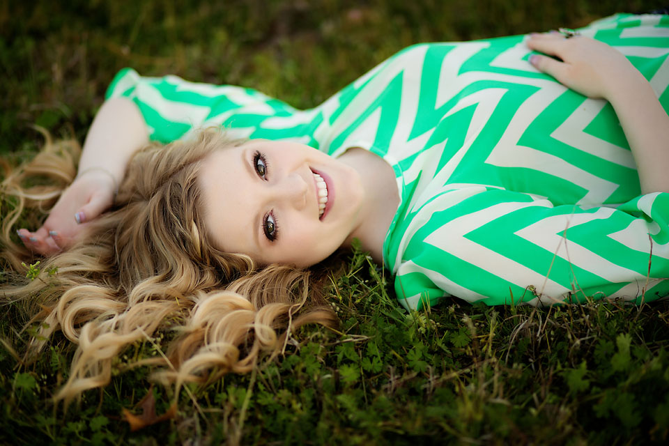 Senior girl portrait laying in grass.
