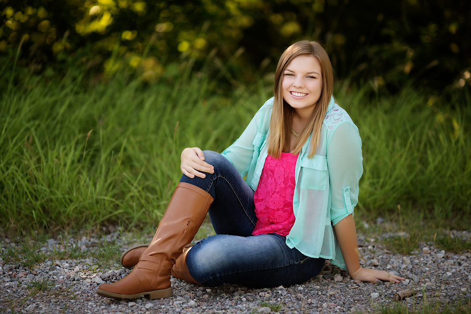 Senior girl portrait wearing layers and boots outdoors.