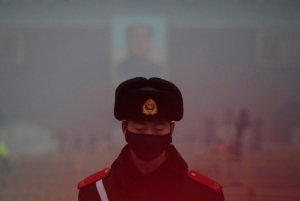 A paramilitary officer in Beijing wears a mask after a red alert was issued for heavy air pollution in 2016.   Jason Lee/Reuters