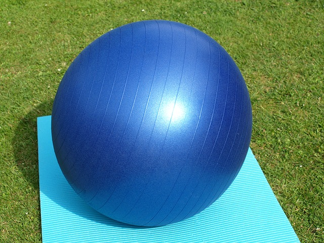blue exercise ball for labor and bouncing a newborn, outside on green grass