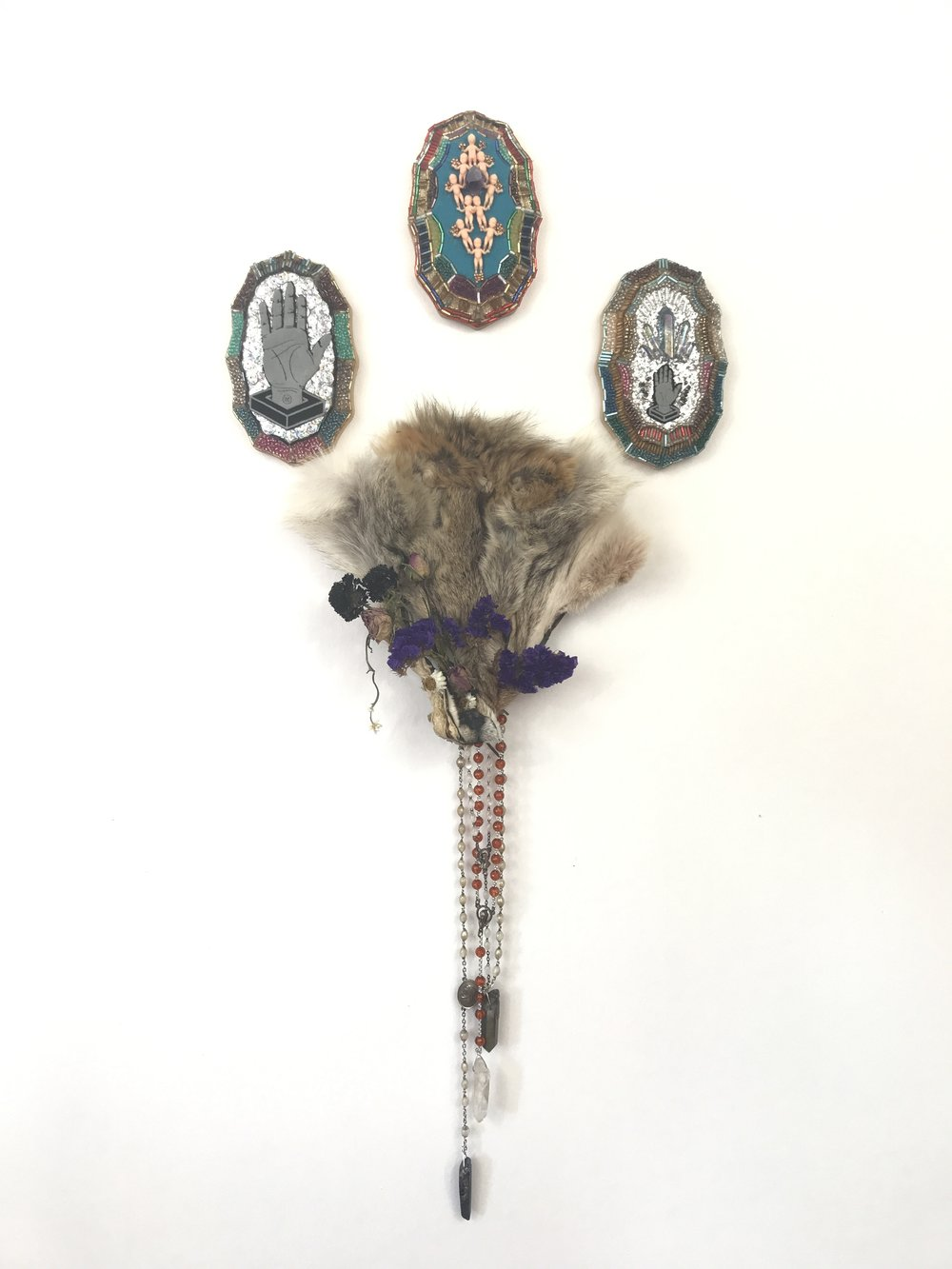 Nunca Más  - Multimedia assemblage (coyote skin, dried flowers, rosary beads, crystals, sequins, miniatures), 2017