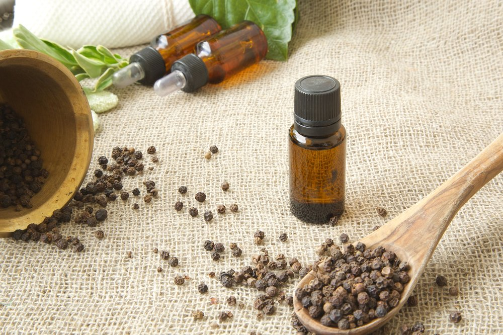 35978321 - a dropper bottle of black pepper essential oil. black pepper in the background.