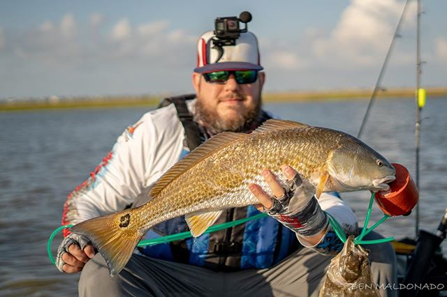 @bullets_broadheads_and_hooks grinning after he landed this hoss! #kayakfishing #redfish