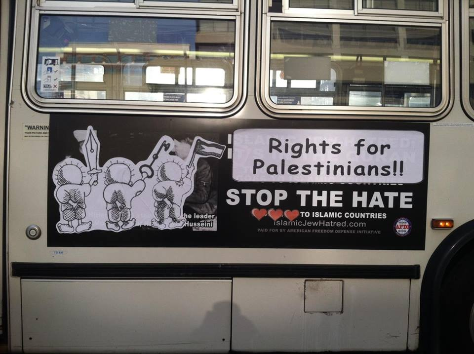 This work - covering an Islamophobic bus ad from AFDI - honors cartoonist Naji al-Ali and the Palestinian struggle for human rights. al-Ali drew over 40,000 cartoons on Palestinian and Arab politics and political leaders. He is well known as the creator of the character Handala, an icon of Palestinian resistance, pictured here. al-Ali was assassinated in 1987 outside the London offices of the Kuwaiti newspaper that published his work. 2015.  More info.