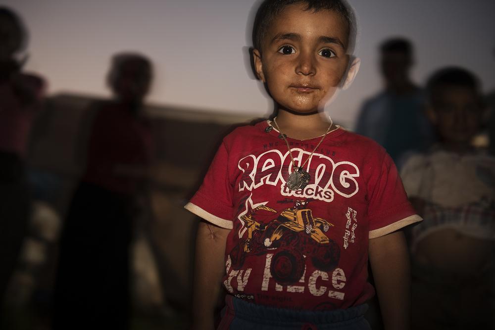 John Mohamed, a Kurdish child, poses for camera in informal refugee camp. Southern Turkey. 2015.©Go Nakamura photography