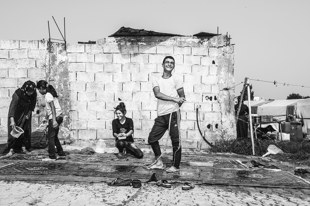 a Kurdish family wash floor carpet for their tent house as a part of preparation for Muslim holiday Eid al fitr in informal refugee camp. Southern Turkey, 2015   ©Go Nakamura     photography