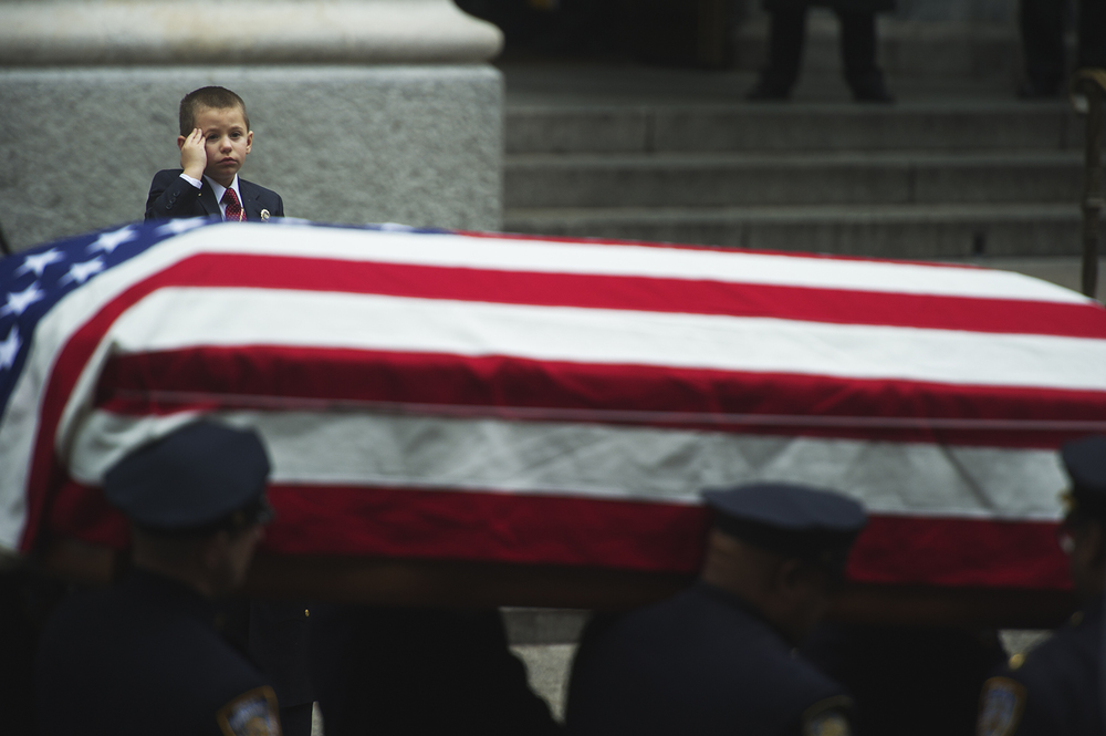 Son of Joseph Lemm salutes as he sees his father in casket off. Joseph Lemm was an NYPD officer, killed in Afghanistan. Manhattan, NY. 2015  ©    Go Nakamura     photography