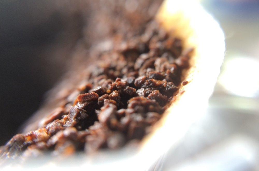 Partículas de café torrado e moído após extração (aumento de 10x).