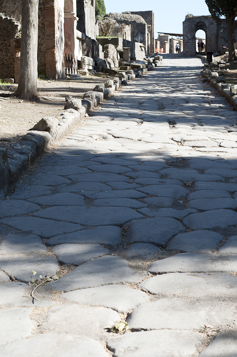 A paved roadway passes crypts as it leads into Pompeii city center