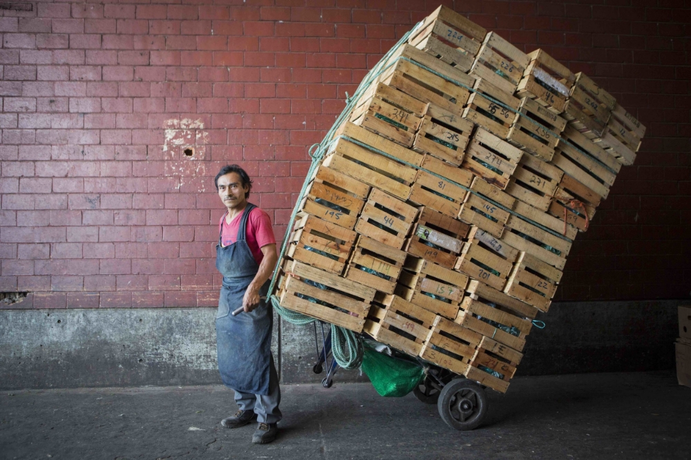 Emilio Santana has worked in Mexico City's Central de Abasto market for three years, after moving to the capital from his home state of Hidalgo. He is delivering vegetables to a client in the parking lot, who will truck them to a roving street market in the northern neighborhood of Indios Verdes.
