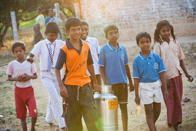 Children carry milk from the dairy to the village's collection point.