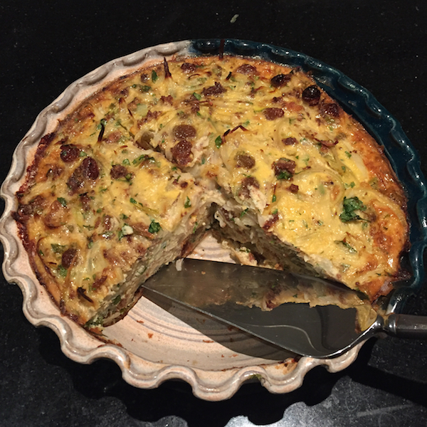 Tart in Ymbre Days, as prepared by the author. It's basically an onion fritatta, dotted with raisins, and delicious with a salad.