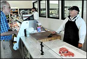 Willie Hughes, butcher at Smith Brothers Butcher Shop, talks with a customer.