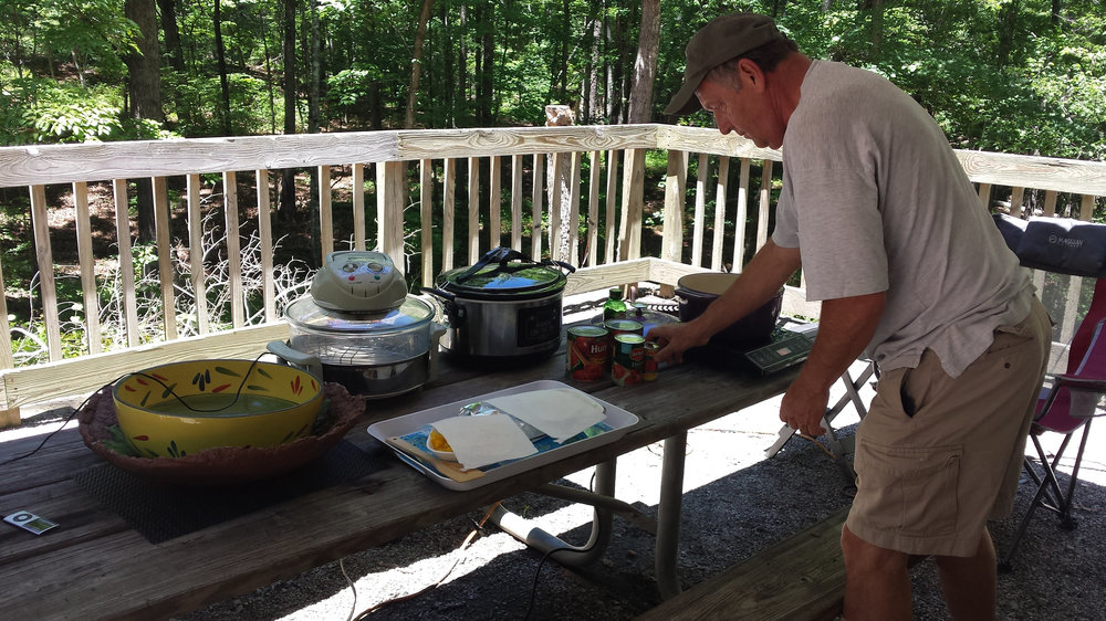 Jim cooking with the induction burner, table-top oven, and crockpot