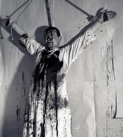 Hermann Nitsch, 1. Aktion 19.12.1963, Kreuzigung und Beschüttung eines menschlichen Körpers Wohnung Mühl.
